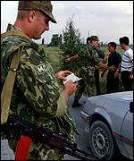 [ image: A Russian soldier checks a Kosovo Albanian's papers]