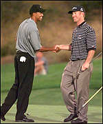 [ image: Friends again: Duval congratulates Woods on his $1.1m victory]