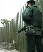 [ image: Past tension: A policeman mans a security barrier on Derry's walls]