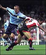 [ image: Lee Bowyer of Leeds holds off Francis Benali's challenge]