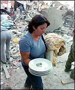 [ image: A survivor carries her plates intact from the debris]