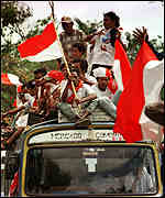[ image: Anti-independence demonstrators wave Indonesian flags at a rally in Dili]