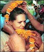 [ image: Sonia Gandhi is garlanded by supporters to celebrate the fall of BJP-led coalition]