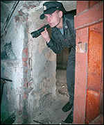 [ image: A policeman checks the cellar of a block of flats]