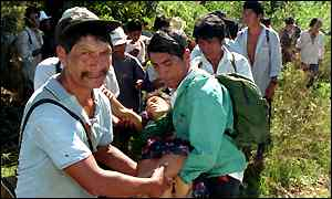 image: [ Guadulupe Mendez Lopez is carried away by Zapatista supporters after she was fatally injured by police ]