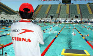 image: [ A Chinese swimming coach watches a team training session ]