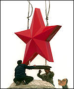 [ image: A giant red star is lowered into place in Tiananmen Square]