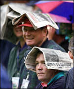 [ image: Spectators shelter from the rain before severe storms held up morning play]