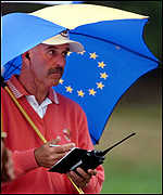 [ image: European captain Mark James plans his strategy in the rain]
