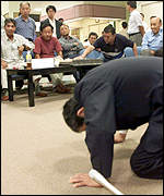 [ image: JCO President Koji Kitani kneels to appologise in front of the to affected local residents]