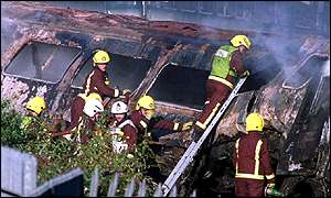 Firemen attend to the smouldering wreck of one of the trains
