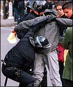 [ image: Police in Paris frisk a protester]