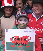 [ image: A Young Welsh fan is flanked by two Japanese supporters]