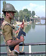 [ image: An Indian soldier guards a bridge in Kashmir]
