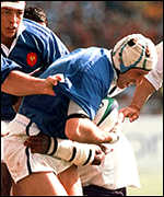 [ image: French flanker Olivier Magne surges on, watched by team-mate Abel Benazzi]