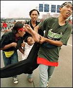 Megawati supporters carry off a wounded colleague