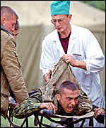 [ image: A surgeon cuts clothes from a wounded Russian soldier]