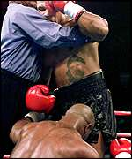 [ image: Tyson had to be restrained by referee]
