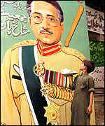 [ image: A tea boy admires a mural of Pakistan's new ruler]