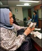 [ image: A Muslim woman buys US dollars at a money exchange in Jakarta]