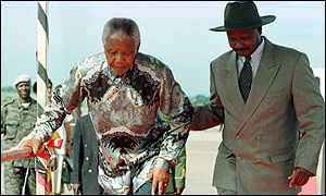 image: [ Nelson Mandela is given a helping hand by President Museveni ]