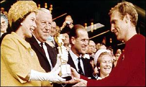 image: [ Bobby Moore receives the 1966 World Cup from Her Majesty the Queen ]
