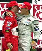 [ image: Hakkinen comisserates Ferrari's Eddie Irvine on the podium]