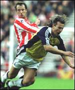 [ image: David Ginola goes down under a challenge from Nicky Sumerbee]
