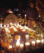 [ image: An Indian woman watches over the candle-lit grave of a relative in Tzintzuntzan]