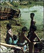 [ image: Child victims stand near an overturned policevan in flooded fields]