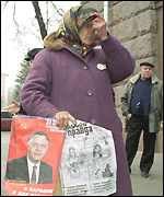 [ image: A woman crosses herself, clutching a poster of Symonenko]