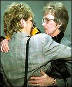 [ image: A victim's relatives embrace each other after the sentencing]