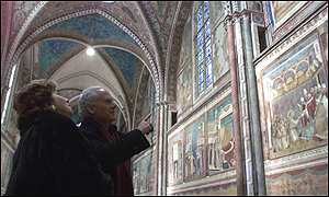 People look at frescoes in the main aisle
