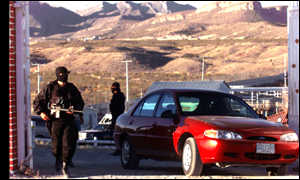 Police guard a convoy of cars at the ranch