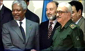 image: [ Kofi Annan and Tariq Aziz shake hands after speaking to reporters ]