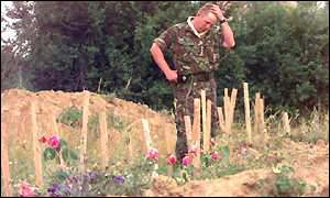 A Nato soldier stands next to a mass grave in the village of Kacanik