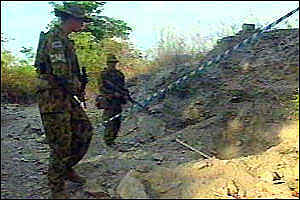 UN soldiers guarding the site of a mass grave
