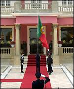 The Portuguese flag is lowered in front of the government palace