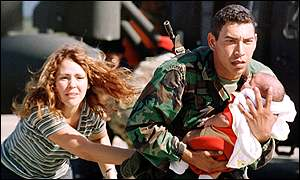 A mother and baby are helped to safety by a Venezuelan paratrooper