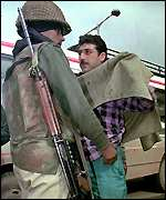 An Indian soldier searches a civilian