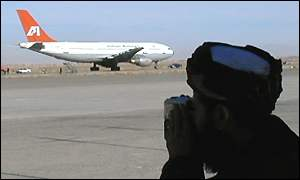 A Taleban guard keeps watch on the aircraft at Kandahar airport