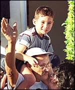 Elian Gonzalez rides on his great uncle Delfin Gonzalez' shoulders