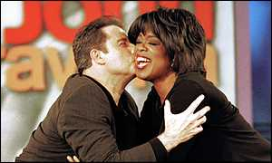 image: [ Oprah greets John Travolta on Thursday: she has filmed her show in Amarillo throughout the trial ]