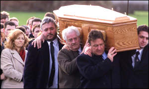 Richard Jameson's widow (left) follows his coffin