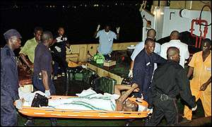 A survivor calls out a prayer as he is brought ashore from a rescue boat