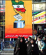 Iranians walk past a poster urging them to vote