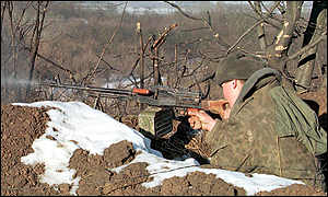 A soldier fires from a trench in Vedeno gorge in south Chechnya