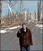 An elderly resident of Grozny carries a white flag for protection