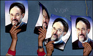 People hold up posters of Mohammad Khatami