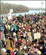 Banner-waving protesters on the banks of the River Tisza